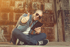 Young man listening to music with headphones via tablet Stock Images