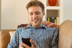 Young man listening to music on his couch Stock Image