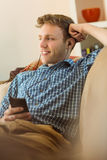 Young man listening to music on his couch Royalty Free Stock Photos