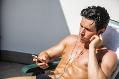 Young Man Listening To Music On Lounge Chair Stock Photo