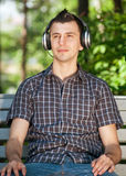 Young man listening to music outdoors. Portrait of a relaxed young man sitting on bench in park and listening to music on headphone royalty free stock photos