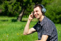 Young man listening to music outdoors Stock Images