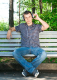 Young man listening to music outdoors. Portrait of a relaxed young man sitting on bench in park and listening to music on headphone Royalty Free Stock Photo