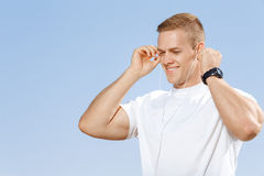 Young man listening to music outdoors Stock Photo