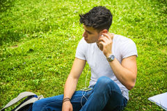 Young Man Listening to Music in Park Stock Image