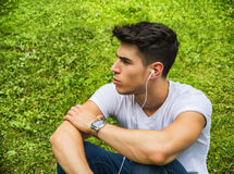 Young Man Listening to Music in Park Royalty Free Stock Image