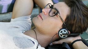 Young Man Listening to Music in Park stock footage