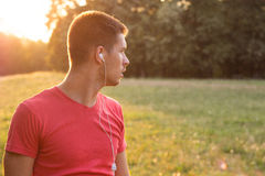 Young man listening to music in park Royalty Free Stock Photos