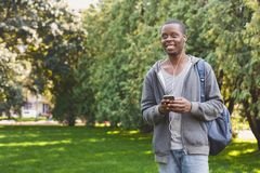 Young man listening to music in park outdoors. Young smiling african-american man standing in park, using smartphone and listening to music with earphones Royalty Free Stock Photo