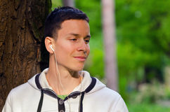 Young man listening to the music in the park Stock Image