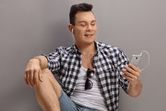 Young man listening to music on a phone Stock Photos