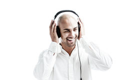Young man listening to music and puts his hands at the earphones Royalty Free Stock Photos