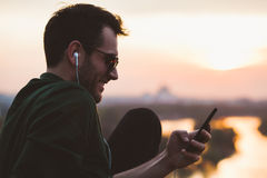 Young man  listening to the music on the smartphone Stock Photos