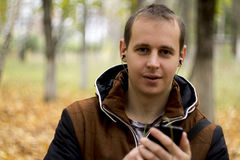 Young man listening to music on smartphone. On the nature Stock Image