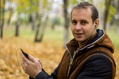 Young man listening to music on smartphone. On the nature Stock Photography