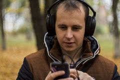 Young man listening to music on smartphone. On the nature Royalty Free Stock Photos