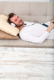 Young man listening to music on the sofa Stock Photos