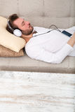 Young man listening to music on the sofa Stock Images