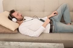 Young man listening to music on the sofa Royalty Free Stock Image