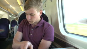Young Man Listening To Music On Train Journey Stock Image