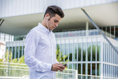 Young Man Listening to Music Using Earphones in City Royalty Free Stock Photography