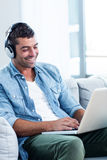 Young man listening to music while using laptop Stock Photography