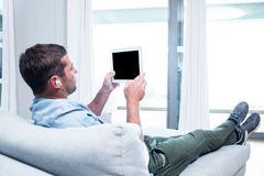Young man listening to music while using tablet Stock Image