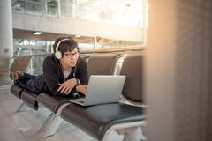 Young man listening to music waiting in airport terminal Stock Images