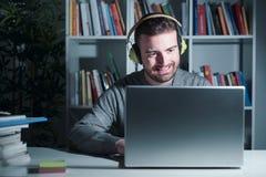 Man watching movies sitting at the desk at night Stock Photo