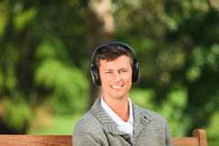 Young man listening to some music. On the bench Stock Photos