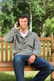 Young man listening to some music on the bench. Young cute man listening to some music on the bench Royalty Free Stock Images