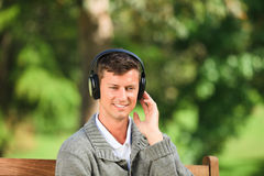 Young man listening to some music on the bench. In the park Stock Photography