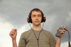 Young man listens music in headphones Royalty Free Stock Photos