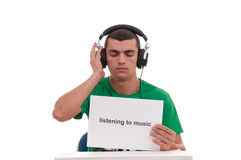 Young man listens music with headphones and holds in his hand a paper Royalty Free Stock Images