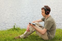Young man listens music sits on ashore Stock Image