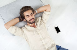 Young man listing to music with mobile phone Stock Images