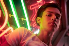 Young man, lit by neon light at night. royalty free stock photography
