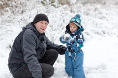 Young man and little boy having fun with snow Royalty Free Stock Image