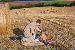 Young man and little boy making picnic on hay field Royalty Free Stock Image