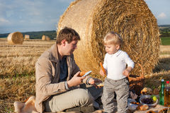 Young man and little boy making picnic on hay field Stock Images