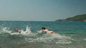 Young man and little girl bathe in sea on sunny afternoon. Male standing in water, gaily calls cute daughter to him, she quickly dives and they continue stock video footage