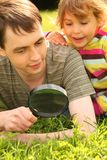 Young man and little girl look through magnifier. Young man and little smiling girl look through magnifier stock photos