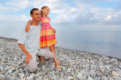Young man with little girl on stony beach Royalty Free Stock Image