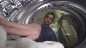 Young man is loading laundry in washing machine. View from inside.  stock video footage