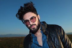 Young man with long beard and glasses. Looking at the camera against blue sky Stock Image