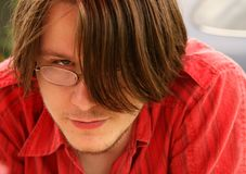 Young man with long fringe. Portrait of young man with glasses looking out under long hair fringe Stock Image