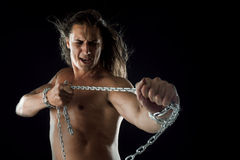 Young man with long hair breaks the iron chain. Strong. Concept of resistance Royalty Free Stock Photo