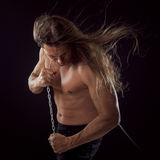 Young man with long hair dragging something behind him. Strong. Young man with long hair dragging something behind him royalty free stock photography