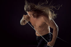 Young man with long hair dragging something behind him. Strong. Young man with long hair dragging something behind him stock photos