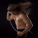 Young man with long hair dragging something behind him. Strong. Royalty Free Stock Photos